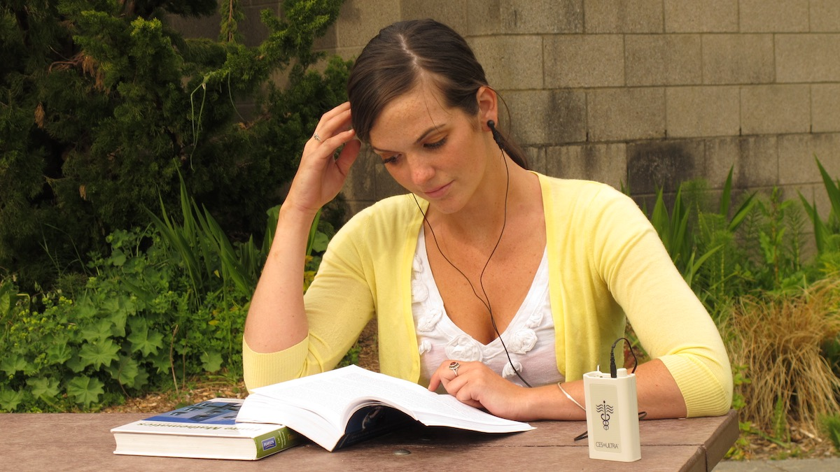 College student using a CES Ultra device to relax while reading a textbook