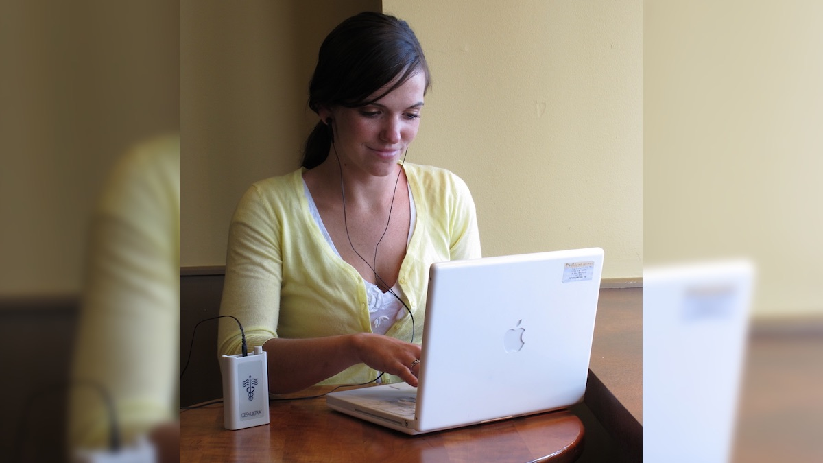 Person using a CES Ultra device to relax and increase focus while using a laptop computer